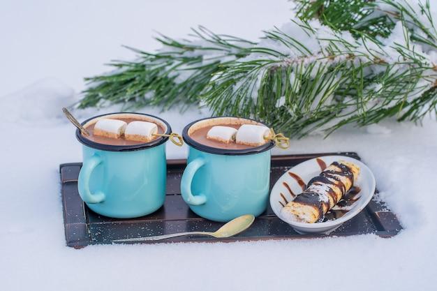 눈과 흰색 배경의 침대에 두 개의 뜨거운 코코아 음료를 닫습니다. 크리스마스 겨울 아침의 개념