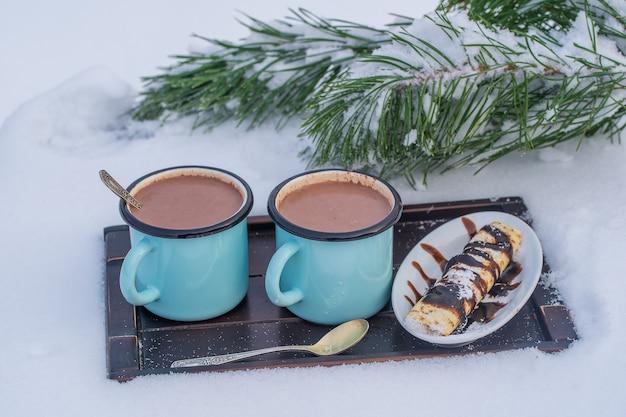 눈과 흰색 배경의 침대에 두 뜨거운 코코아 음료를 닫습니다. 크리스마스 겨울 아침의 개념
