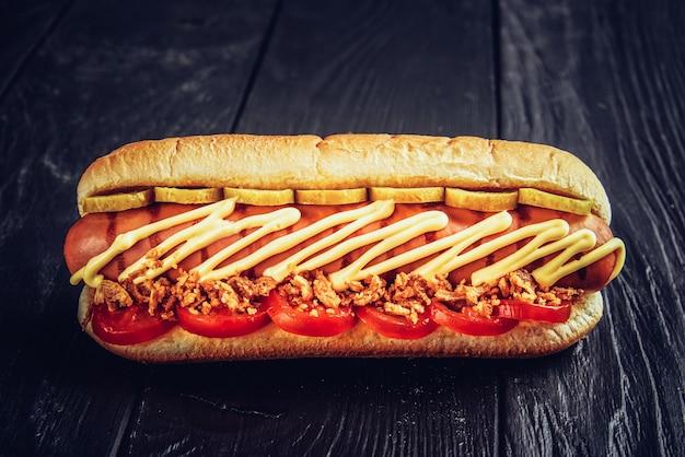 Два хот-дога с крупным планом кетчупа, желтой горчицей и луком на серой деревянной поверхности.