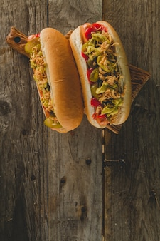 Two hot dogs on wooden surface