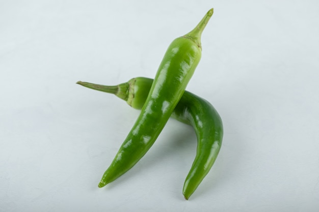 Two hot green chili peppers on white background.