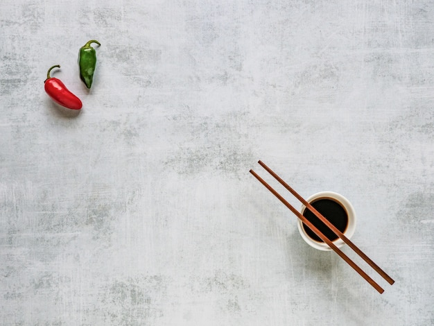 Two hot peppers and soy sauce with chopsticks. food background.