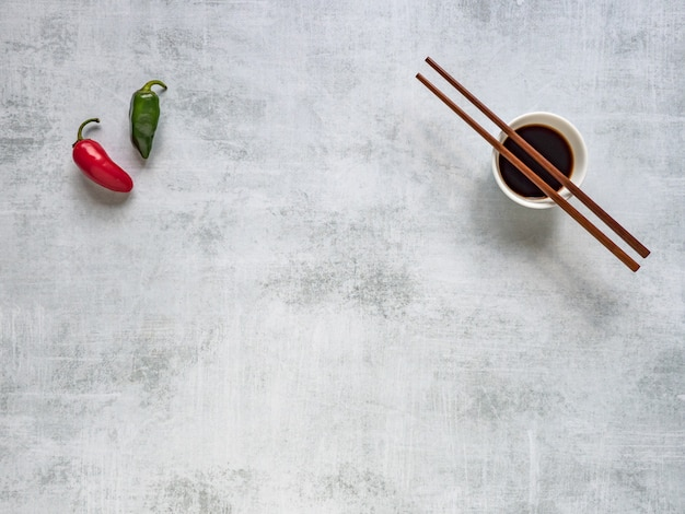 Two hot peppers and soy sauce with chopsticks.