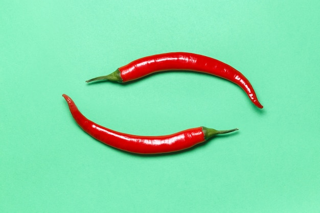 Two hot red chili peppers form yin yang a symbol on green . flat lay.