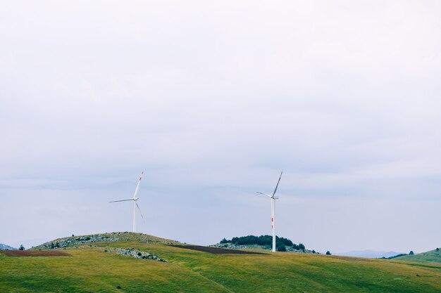 흐린 하늘을 배경으로 푸른 언덕 사이에 두 개의 거대한 풍력 터빈
