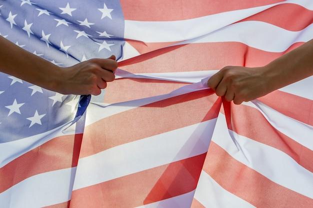 アメリカの国旗を保持している2つの人間の手。アメリカ合衆国独立記念日のコンセプトのお祝い。