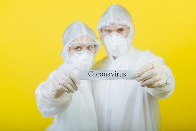 개인 보호 복 (ppe)을 입은 두 명의 의사가 코로나 바이러스라는 텍스트가있는 경고 표지판을 들고 있습니다. 노란색 배경