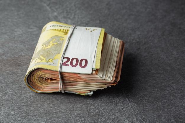 Банкнота евро 200 в пачке или круглой резинке для денег изолированных на серой предпосылке.