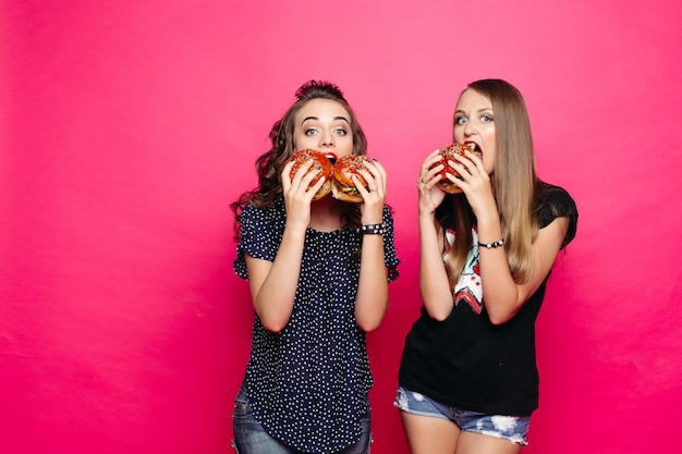 Two hungry friends with hamburgers over bright pink