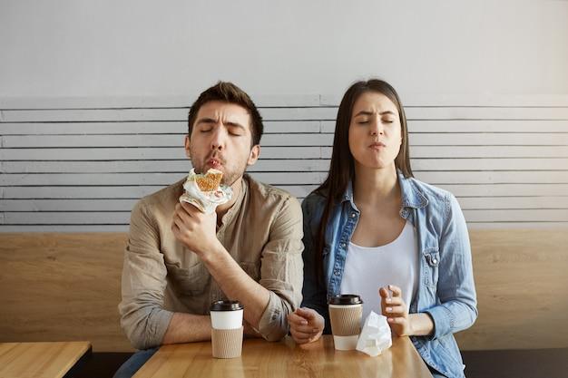 長い一日の勉強の後、食堂で食事をした2人の空腹の学生。大きな満足感でサンドイッチを食べる若いペア。