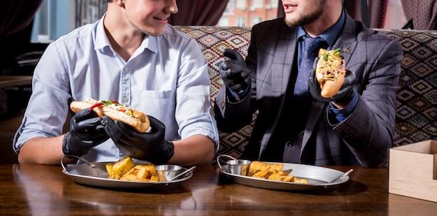 카페에서 핫도그를 먹는 두 배고픈 젊은이. 레스토랑