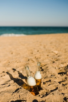 Two ice cold beer bottles in the sand under the bright sun at beach