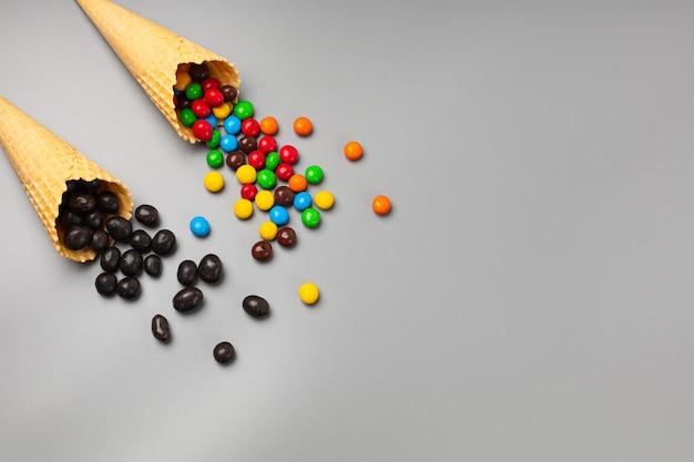 灰色の背景に異なるお菓子を持つ2つのアイスクリームコーン