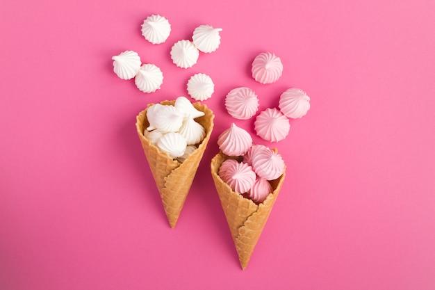 ピンクの背景の中央に白とピンクのメレンゲの2つのアイスクリームコーン。上面図。スペースをコピーします。