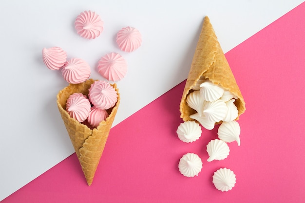 二色の背景に白とピンクのメレンゲと2つのアイスクリームコーン。上面図。