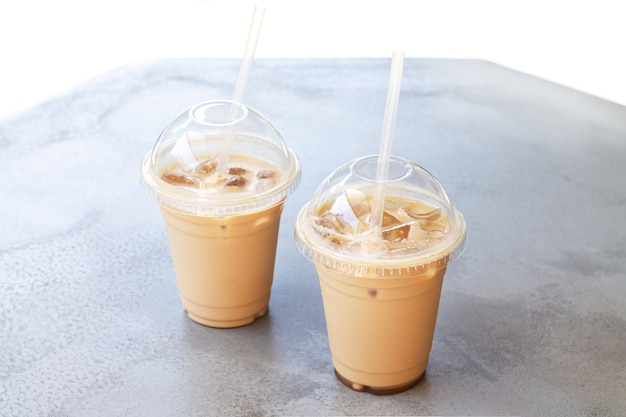 Two iced coffee or latte in take away plastic cup on street cafe stone table