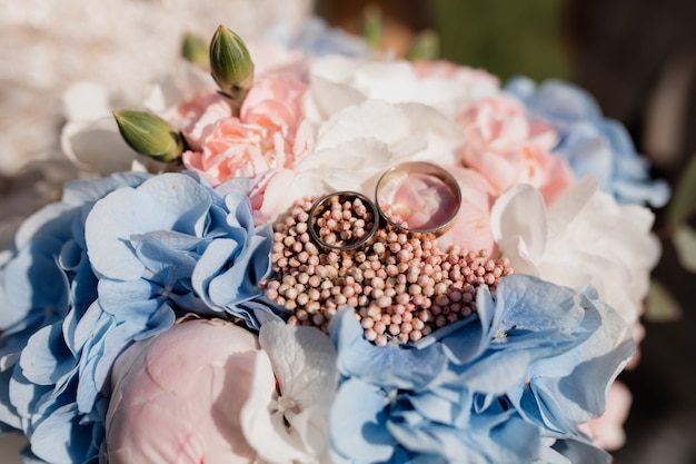 Two identical wedding rings lie on a wedding bouquet