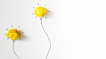 Two illuminated crumpled yellow paper light bulb on white background