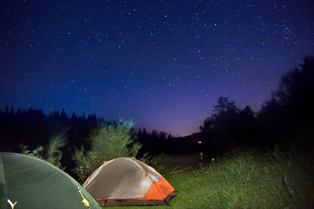 Two illuminated tents at mountains under dark night sky with many stars