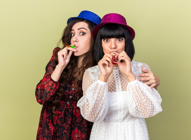 Two impressed party girls wearing party hat both blowing party horn one putting hand on another girl's shoulder isolated on olive green wall