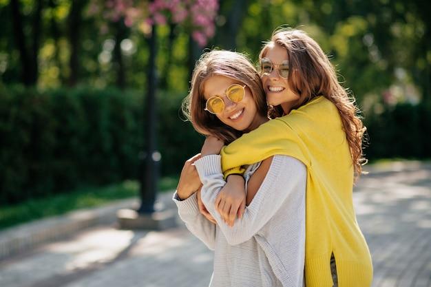 明るいサングラスとセーターを着た2人の信じられないほどの女の子が路上でハグし、前向きな気分、真の感情。路上で2人の若い女性の屋外のポートレート