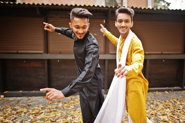 Two indian stylish mans friends in traditional clothes dancing outdoor. navaratri dance.