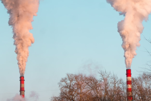 Two industrial chimneys with heavy sunset pink smoke causing air pollution on the blue sky