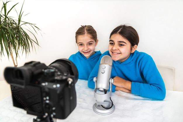 Two influencers sisters and bloggers broadcasting live from their living room laughing and looking at camera and talking into the microphone on a video or social networking platform