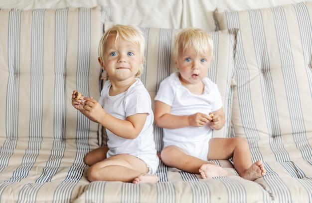 순진한 두 아기가 쿠키를 즐기고 있습니다. 거실에 있는 소파에서 비스킷을 먹고 있는 파란 눈과 금발 머리를 가진 쌍둥이의 초상화. 아기의 재미있는 사진, 함께 과자를 먹는 동일한 아이들