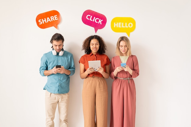 소셜 네트워크에서 서로 의사 소통하면서 모바일 장치에서 스크롤하는 캐주얼웨어를 입은 두 명의 이문화 소녀와 청년