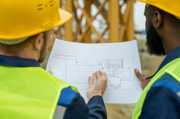 Два межкультурных строителя-мужчин обсуждают эскиз нового строительства
