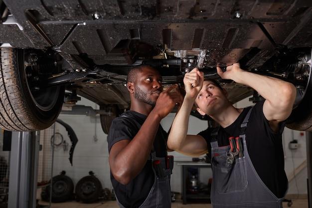 Два межрасовых разных механика проверяют дно машины в автосервисе
