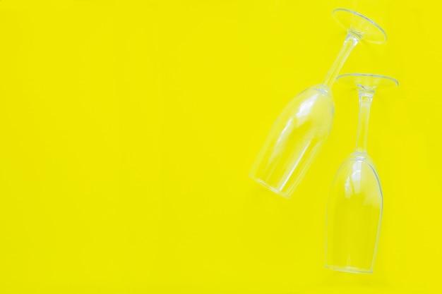 Два перевернутых бокала лежат на желтом фоне, вид сверху, плоская копия пространства, изолировать