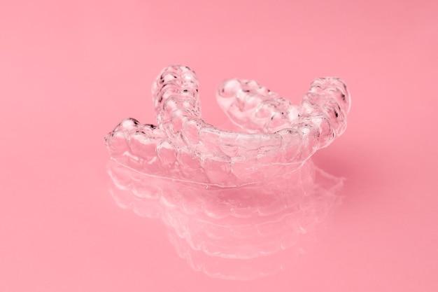 분홍색 배경에 두 개의 보이지 않는 치과 치아 정렬 기. 정렬 후 치아를 고정하기위한 교정 용 임시 탈착식 교정기. 괄호 후 치료.