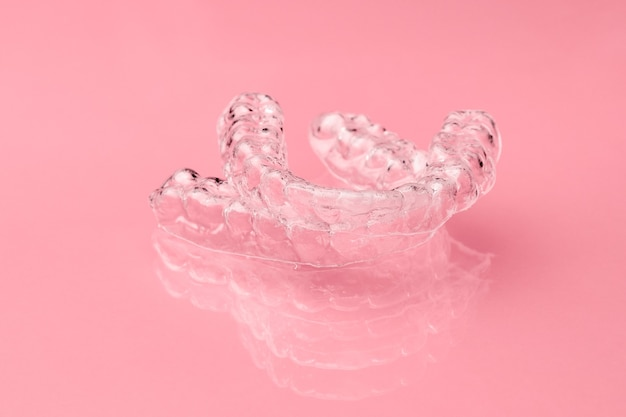 Two invisible dental teeth aligners on the pink background. orthodontic temporary removable braces for fixing teeth after alignment. therapy after brackets.