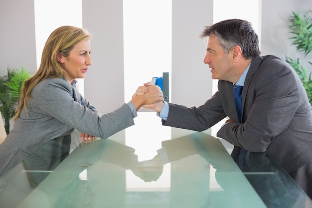 Two irritated businesspeople having an arm wrestling sitting around a table