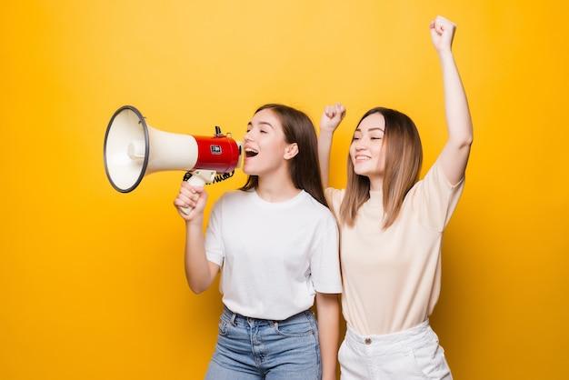 두 염증 된 젊은 여자 여자 친구 노란색 벽에 고립 된 확성기에서 비명. 사람들의 라이프 스타일 개념. 복사 공간을 모의합니다.