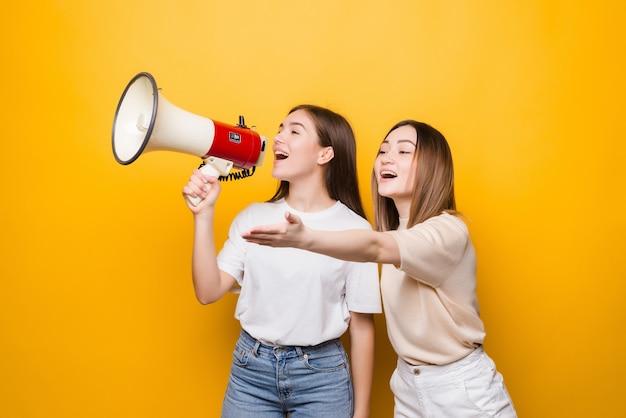 Два раздраженных друга девушек девушек кричат в мегафон, изолированный на желтой стене. концепция образа жизни людей. копируйте пространство для копирования.