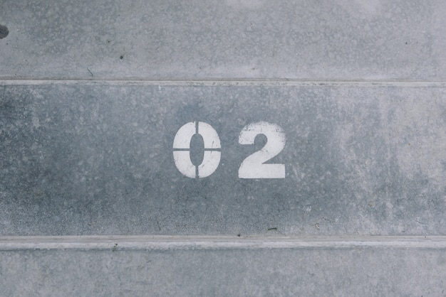 Two is written on concrete in white paint