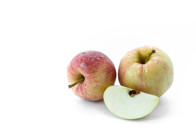 Два изолированных яблока с кусочком капель воды на белом фоне