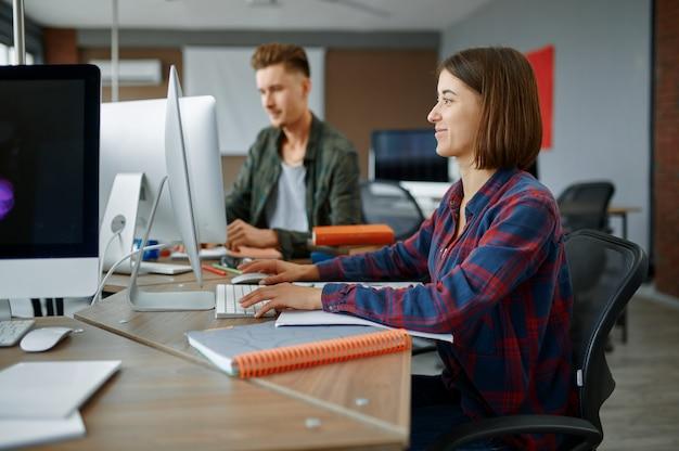 В офисе за компьютерами работают два ит-специалиста. веб-программист или дизайнер на рабочем месте, творческое занятие. современные информационные технологии, корпоративная команда