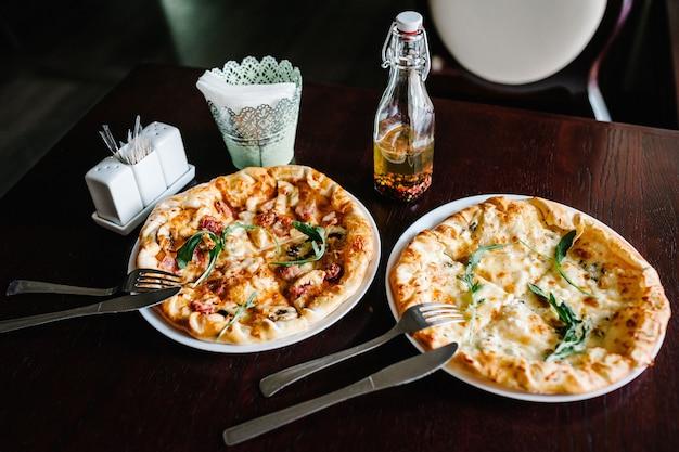 茶色の木製の机の表面にルッコラの肉と2つのイタリアンピザ4チーズ