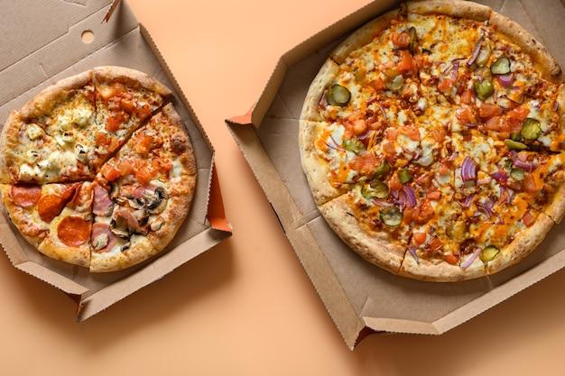 トマト、タマネギ、モッツァレラチーズ、ソースが入ったカートンボックスに入った2つのイタリアンピザ