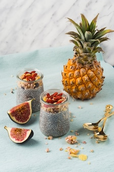 Two jar of smoothie with pineapple and fig slices over place mat