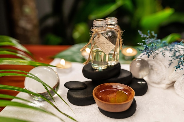 Two jars of aromatic oils standing on stones for a therapy stone and located on a terry towel next to which are transparent spheres, a twisted white terry towel