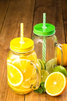 Two jars of detox water with slices of orange and lime