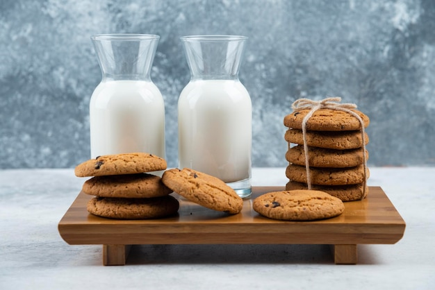 Two jars of milk with delicious cookies .