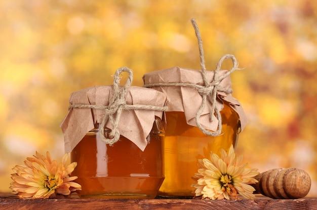 꿀, 노란색 테이블에 나무 drizzler의 두 항아리