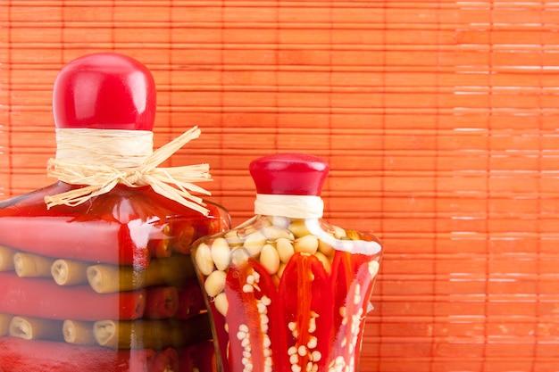 赤い背景の上に漬けたインゲンマメと他の野菜の2つの瓶
