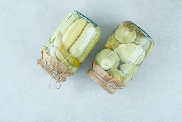 Two jars of pickled vegetables on blue surface.